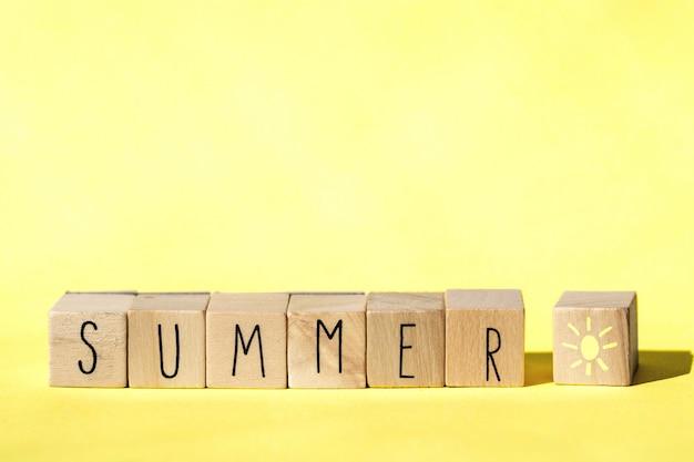 Holzwürfel mit dem wort sommer auf gelbem hintergrund, buntes helles sommerkonzept. heiter
