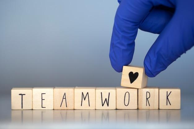 Holzwürfel mit den worten teamarbeit für geschäftskonzept oder krankenschwestern im gesundheitswesen oder arzt covid-19, coronavirus, arbeiten in teams weltweit