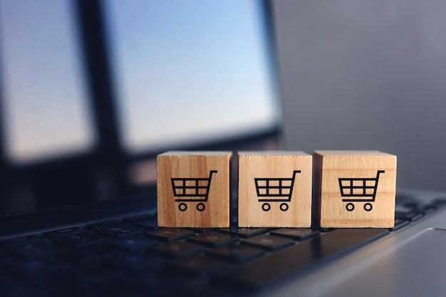 Holzwürfel mit einkaufswagen auf laptoptastatur. online-shopping-konzept
