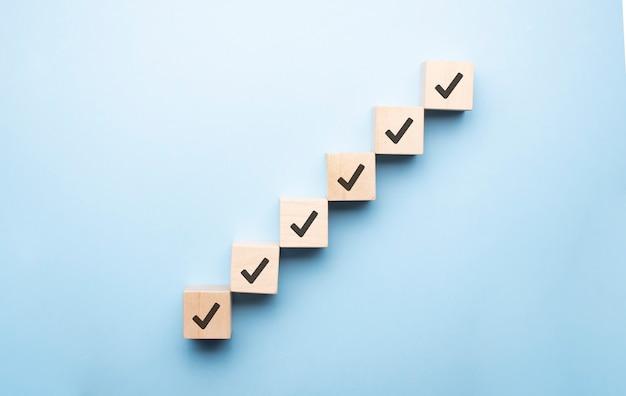 Holzwürfel mit häkchen auf blauem hintergrund, checklistenkonzept, platz kopieren.