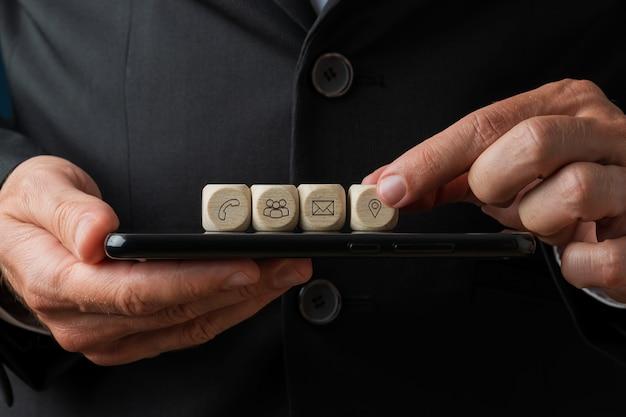 Holzwürfel mit kontakt- und informationssymbolen auf digitalem tablet