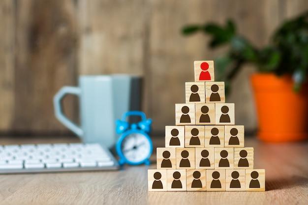 Holzwürfel mit männern, die mit einer pyramide auf dem hintergrund des schreibtischs aufgereiht sind. unternehmenskonzept, finanzpyramide, führung.