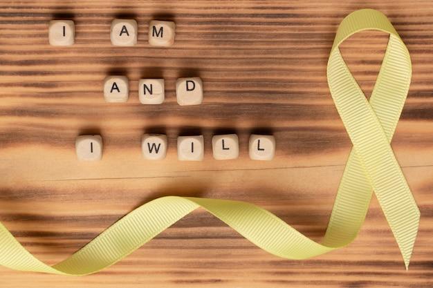 Holzwürfel mit text des slogans des weltkrebstags ich bin und ich werde und ein gelbes band, auf einer holzoberfläche. flach liegen