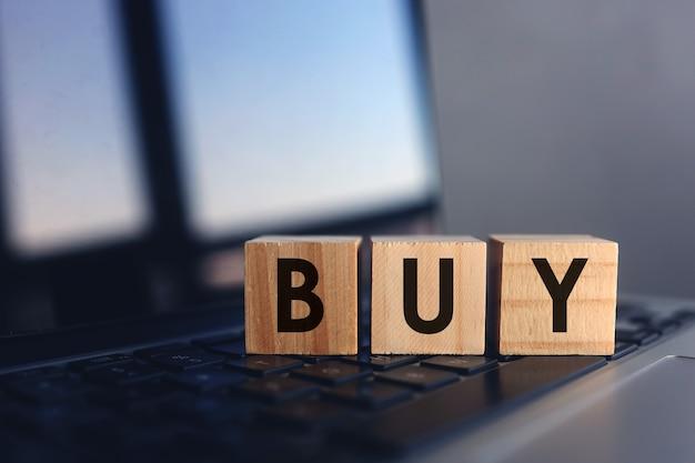 Holzwürfel mit wortkauf auf laptoptastatur. online-shopping-konzept.