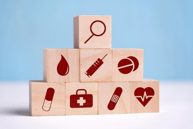 Holzwürfel sind symbole von symbolen mit lupe, analysen, spritze, tabletten, pille, pflaster und herz.
