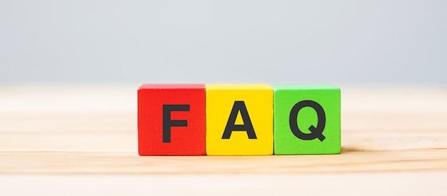 Holzwürfelblöcke mit faq-text (häufig gestellte fragen) auf tabellenhintergrund. finanz-, marketing- und geschäftskonzepte