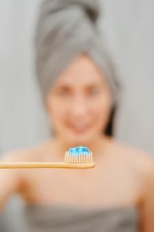 Holzzahnbürste aus bambus mit blauer paste zum aufhellen und zur behandlung von karies. konzept der pflege und zahnmedizin.