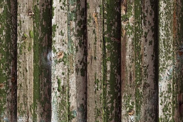 Holzzaun, holzstruktur mit knoten und abblätternder farbe, alte schuppige bretter.