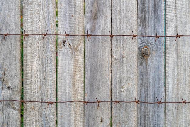 Holzzaun mit rostigem stacheldraht