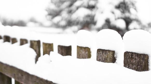Holzzauntor mit weißem schnee bei starkem schneesturm bedeckt, büsche im hintergrund. schnee auf einem holzzaun als hintergrundbild.