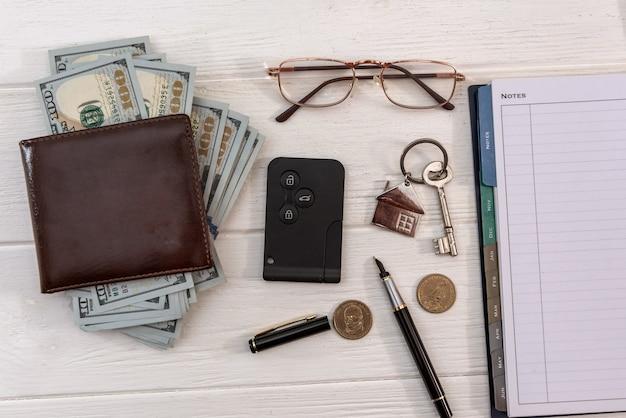 Homa nad autoschlüssel mit dollarnoten auf dem tisch. sparkonzept