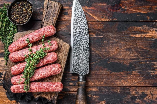 Homamade rohes fleisch lula kebabs würstchen auf einem schneidebrett. dunkler hölzerner hintergrund. draufsicht. speicherplatz kopieren.
