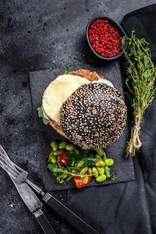 Home craft burger mit einem schwarzen brötchen, rührei und rucola. blackburger. schwarzer hintergrund. draufsicht