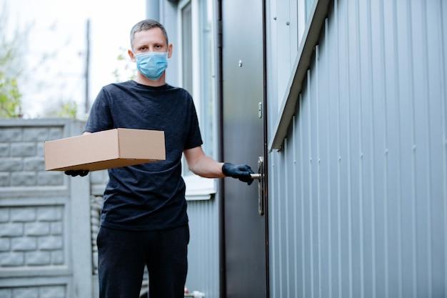 Home delivery shopping box mann mit handschuhen und schutzmaske liefert pakete an der tür.