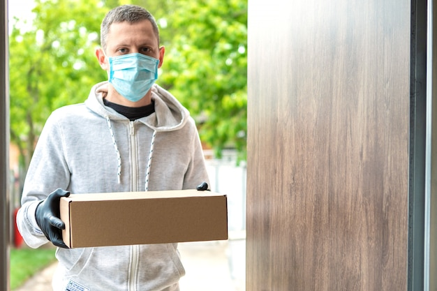 Home delivery shopping box mann mit handschuhen und schutzmaske liefert pakete an der tür