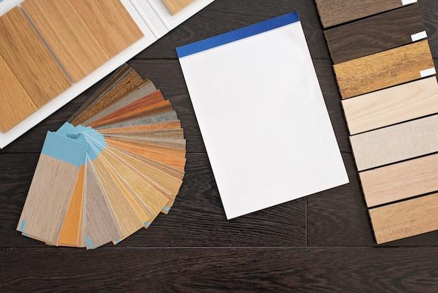 Home design-konzept mit einer probe von natürlichem holzmaterial für kunden. laminat- und vinylboden-designpalette und leeres notizbuch für zeichnungen. bau und reparatur.