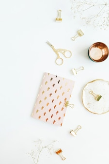 Home-desk-schreibtisch im goldstil mit notizbuch, schere und clips auf weißer oberfläche