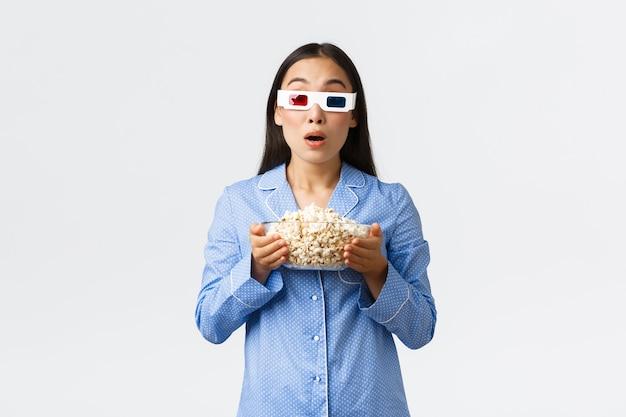 Home freizeit, übernachtung und pyjama-party-konzept. erstauntes und beeindrucktes asiatisches mädchen im schlafanzug, das thriller ansieht, eine schüssel popcorn hält und eine 3d-brille trägt, in ehrfurcht in den fernseher starrt.