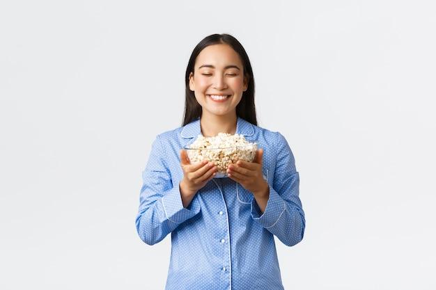 Home freizeit, übernachtung und pyjamaparty-konzept. lächelndes erfreutes asiatisches mädchen, das freien tag im bett mit popcorn genießt, isst und filme im pyjama sieht, stehende weiße wand.