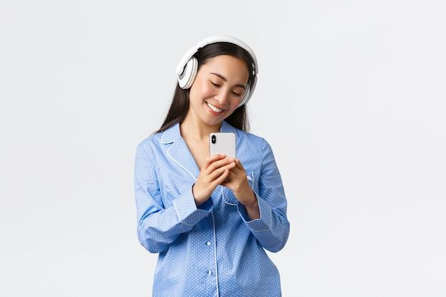 Home freizeit, wochenenden und lifestyle-konzept. wunderschöne weibliche asiatische bloggerin in kopfhörern und pyjama, die selfie im spiegel nimmt und etwas süßes auf dem handy schießt