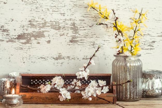Home gemütliche schöne einrichtung, verschiedene vasen und kerzen mit frühlingsblumen, auf einem hölzernen hintergrund, das konzept der innendetails
