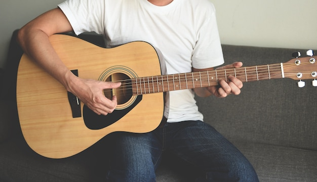 Home hobbys konzept, mann hände spielen akustikgitarre, nahaufnahme gitarrist
