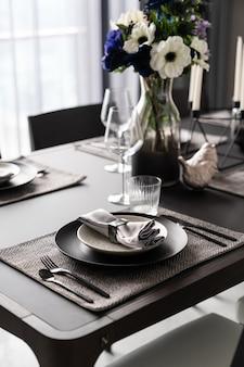 Home inerior mit esstischgedeck mit goldenem edelstahlgeschirr, schwarzem besteck auf nartualer marmorplatte / innenausstattung