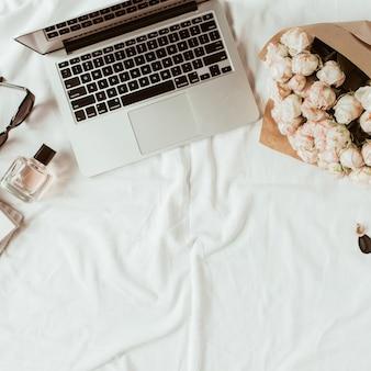 Home-office-arbeitsbereich für mode, schönheit, lifestyle-blogger. laptop, rosenstrauß, damenaccessoires auf weißem leinen