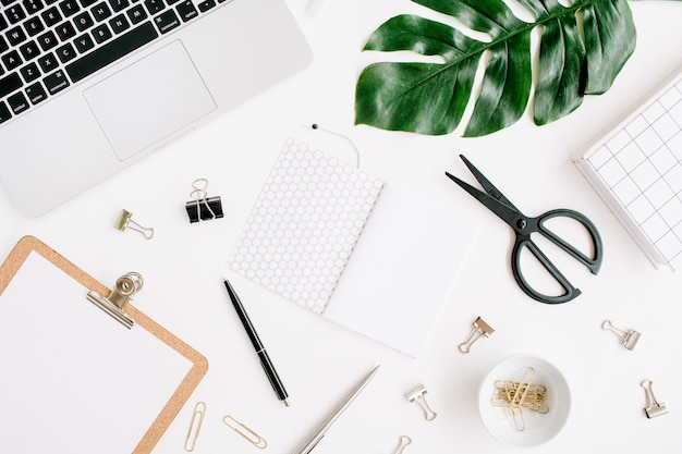 Home-office-arbeitsbereich mit laptop, zwischenablage, palmblatt, notebook und zubehör