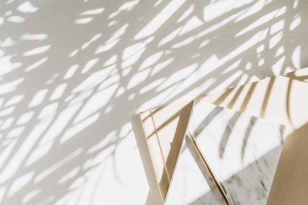 Home-office-arbeitsbereich mit notizbuch auf weiß mit pflanzenschatten