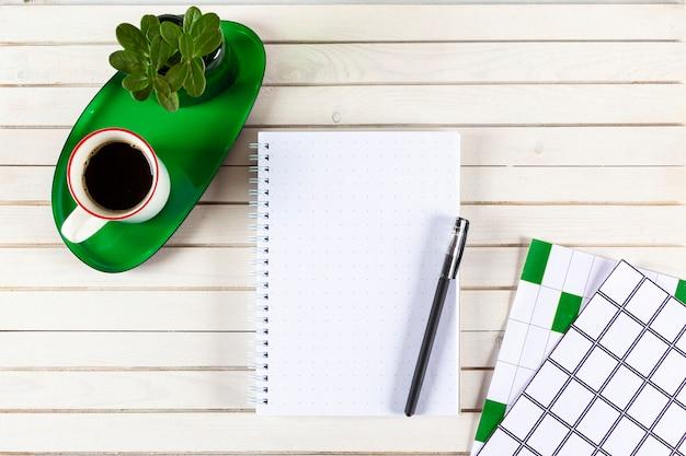 Home-office-arbeitsbereich-modell mit notizbuch, stift, tasse kaffee, pflanze im topf auf holzschreibtisch