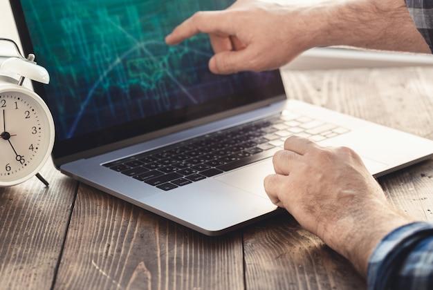 Home-office-arbeitsplatz. mann analysiert und überprüft die grafik auf laptop