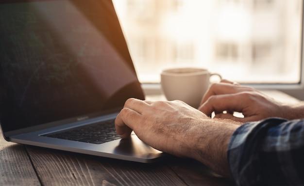 Home-office-arbeitsplatz. mann, der grafik auf laptop-analyse betrachtet, die im hauptbüro sitzt