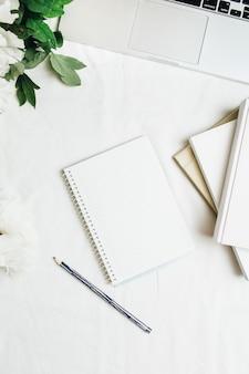 Home-office-arbeitsplatz mit laptop, notebook, weiße pfingstrosen blüht blumenstrauß auf weißem hintergrund. flache lage, ansicht von oben