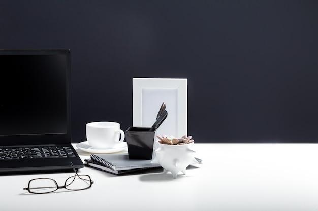 Home-office-laptop-arbeitsplatz. desktop mit laptop-pc smartphone, notizblöcke stifte bürolieferanten tasse kaffee trinken pflanzenblume. weißer schreibtischtisch auf schwarzem hintergrund mit kopienraum.