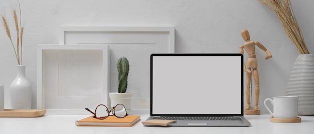 Home office mit mock-up-laptop, notebook, brille und dekorationen auf weißem tisch