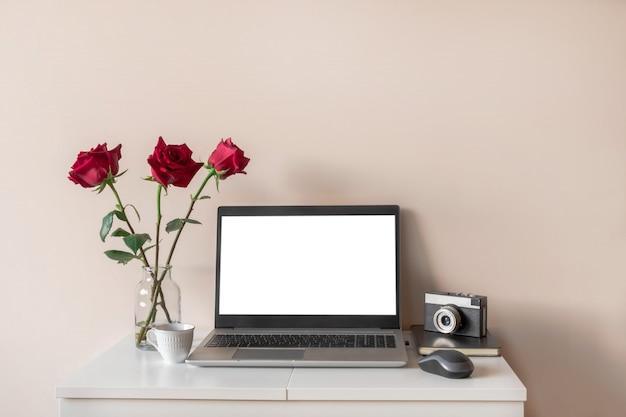 Home-office- oder blogger-konzept, modell. laptop mit weißem isoliertem bildschirm, blumen, retro-kamera auf weißem tisch