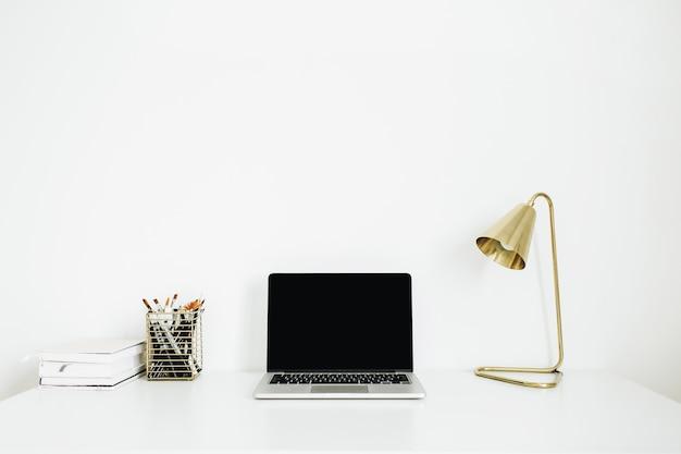 Home-office-schreibtisch arbeitsbereich mit laptop, goldene lampe, briefpapier auf weißer oberfläche.