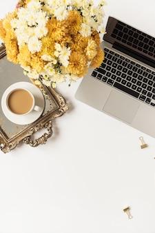 Home-office-schreibtisch arbeitsbereich mit laptop, kaffeetasse, vintage-tablett, herbst wildblumenstrauß auf weiß. flache lage, draufsicht