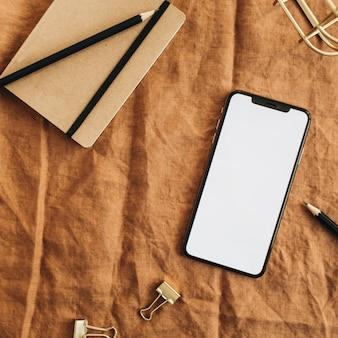 Home-office-schreibtisch arbeitsbereich mit smartphone mit leerem bildschirm auf brauner decke. flache lage, draufsicht minimaler blog-helden-header. Premium Fotos