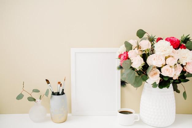 Home-office-schreibtisch mit fotorahmenmodell, schönen rosen und eukalyptusstrauß vor hellem pastellbeige