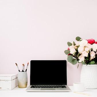 Home-office-schreibtisch mit laptop mit leerem bildschirm, schönen rosen und eukalyptus-blumenstrauß, weißer vintage-sarg vor hellem pastellrosa