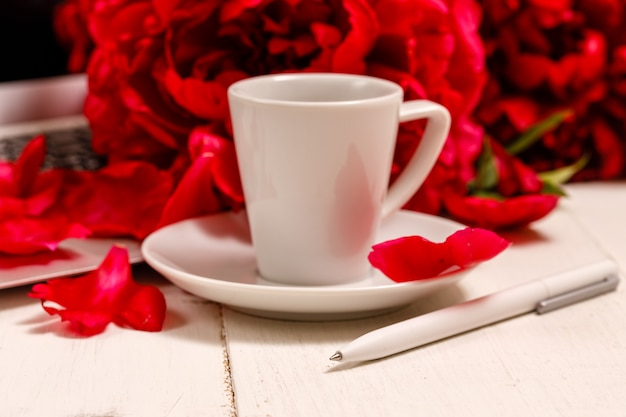 Home-office-schreibtisch mit laptop, rosa pfingstrosen, tasse kaffee, briefpapier, gläser auf weißem hintergrund