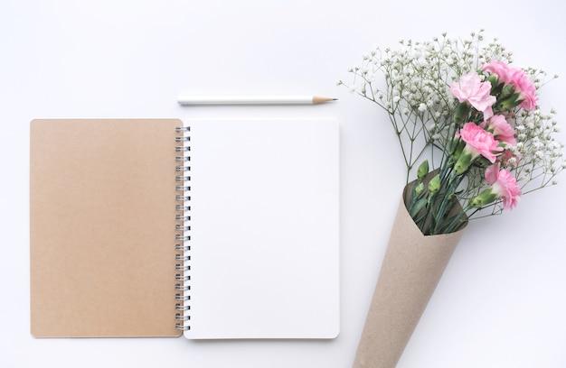 Home-office-schreibtisch tisch mit notizblock, blume auf weißem hintergrund.