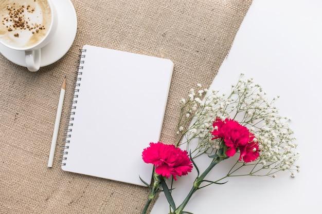 Home-office-schreibtisch tisch mit notizblock, blumenstrauß auf sackleinen hintergrund.