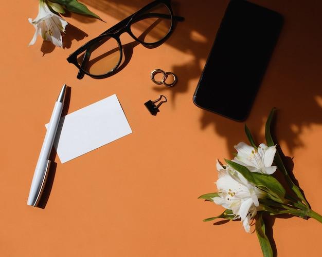 Home-office-schreibtisch. weiblicher arbeitsbereich mit visitenkartenmodell, stift, blumen, brille, ohrringe, briefpapierclip. licht und schatten auf einem ingwerhintergrund. flache lage, draufsicht. markenidentität.
