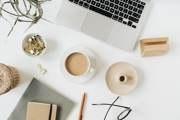 Home-office-schreibtischarbeitsbereich mit laptop, kaffeetasse, notizbuch, brille, stift, grünem pflanzenzweig auf weißer oberfläche