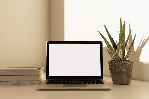 Home-office-schreibtischarbeitsbereich mit laptop mit leerem bildschirm, aloe-ver-heimpflanze im blumentopf, notizbücher auf weißem tisch mit sonnenlichtschatten an der wand