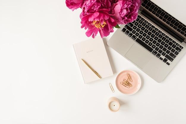 Home-office-schreibtischarbeitsbereich mit laptop, rosa pfingstrosenblumenstrauß und notizbuch auf weiß. flache lage, draufsicht