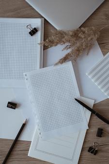 Home-office-schreibtischarbeitsplatz mit leeren papierblättern, laptop, notebook, pampasgras